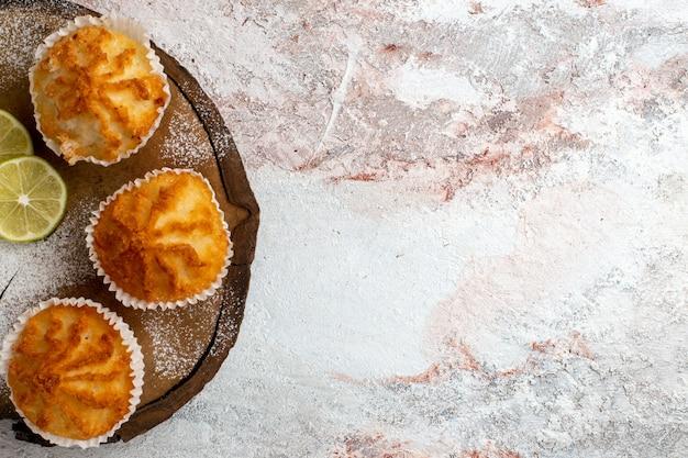 Vista superior de perto bolos doces com rodelas de limão na superfície branca biscoito doce assar bolo torta de açúcar
