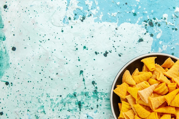 Vista superior de perto, chips picantes dentro do prato na superfície azul-clara