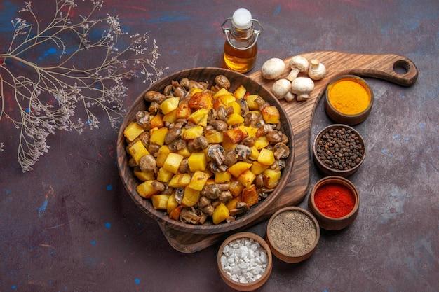 Vista superior de perto com prato de comida com batatas e cogumelos, óleo de cogumelos brancos na garrafa e especiarias coloridas