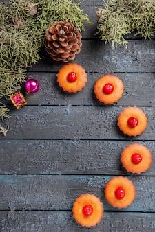 Vista superior de perto cupcakes de cereja arredondados ramos de árvore de abeto brinquedos de natal e um cone em chão de madeira escura com espaço de cópia