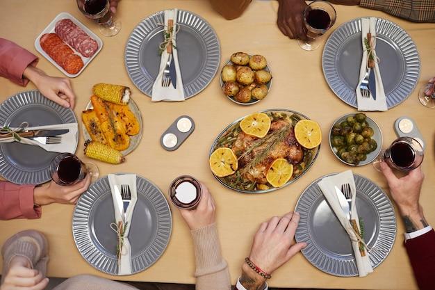 Vista superior de perto de jovens irreconhecíveis sentados à mesa juntos e desfrutando do jantar de ação de graças com amigos e familiares.