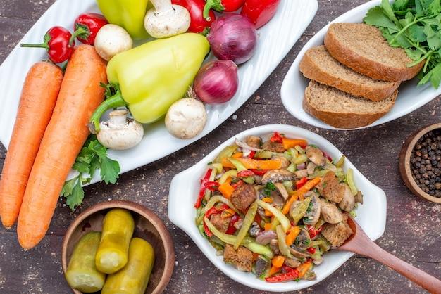 Vista superior de perto deliciosa salada de carne com carne fatiada e vegetais cozidos, juntamente com picles, pão com verduras na carne marrom, prato de refeição alimentar