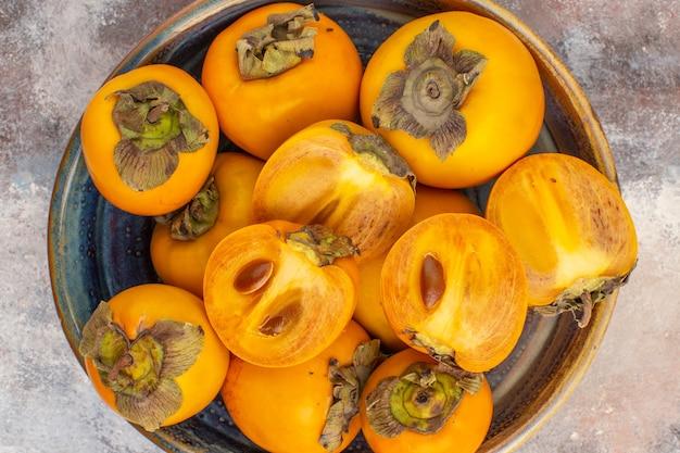 Vista superior de perto deliciosos caquis em caixa de madeira redonda sobre fundo nu