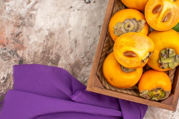 Vista superior de perto deliciosos caquis em um xale roxo de caixa de madeira em um fundo nu