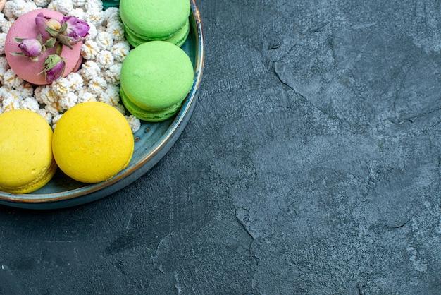 Vista superior de perto deliciosos macarons franceses com doces dentro da bandeja no espaço escuro