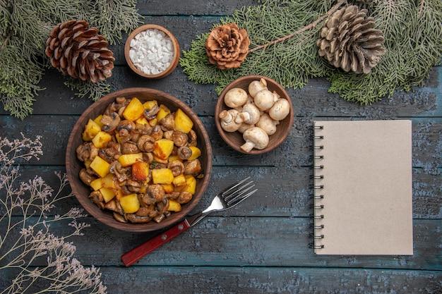Vista superior de perto e prato de ramos de cogumelos e batatas na mesa cinza sob os ramos de abeto com cogumelos cones e sal ao lado do garfo e do caderno