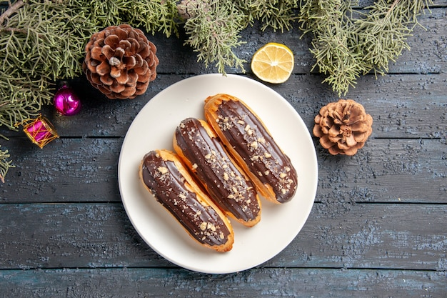 Vista superior de perto éclairs de chocolate em cones de placa oval branca abeto folhas brinquedos de natal fatia de limão em chão de madeira escuro com espaço de cópia