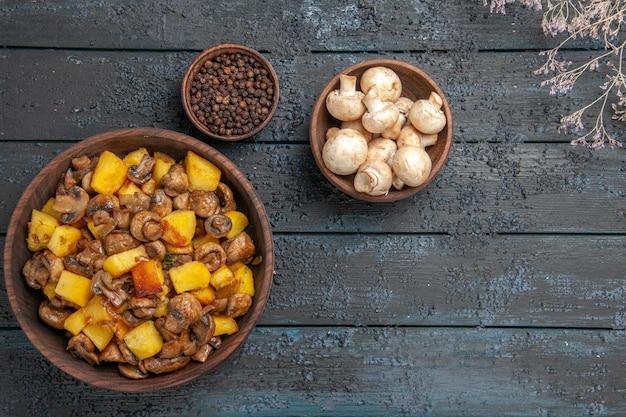 Vista superior de perto em um prato de batatas e cogumelos ao lado de tigelas de pimenta-do-reino e cogumelos brancos