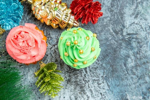 Vista superior de perto enfeites de natal de cupcakes coloridos em fundo cinza