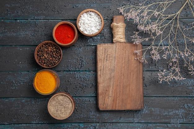 Vista superior de perto especiarias e tábua de cortar entre diferentes especiarias coloridas e ramos na mesa