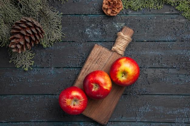 Vista superior de perto frutas a bordo de três maçãs amarelo-avermelhadas em uma tábua de madeira entre galhos com cones
