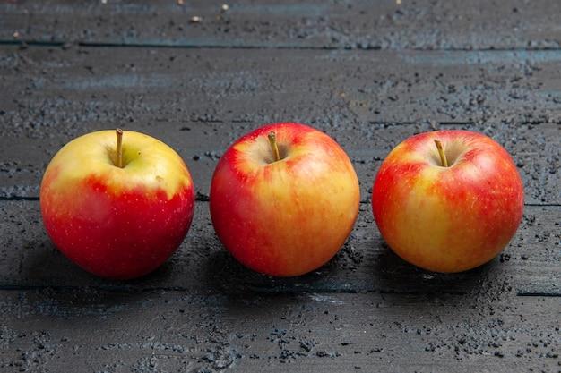 Vista superior de perto frutas três maçãs amarelo-avermelhadas em uma mesa de madeira cinza