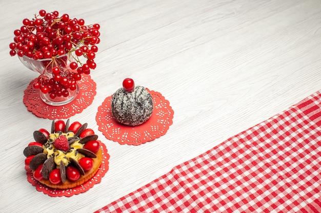 Vista superior de perto groselha em um bolo de frutas de cristal e bolo de cacau no guardanapo de renda oval vermelha e toalha de mesa quadriculada vermelho-branco na mesa de madeira branca