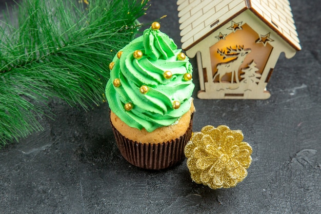 Vista superior de perto mini cupcake de árvore de natal com galho de árvore de natal em fundo escuro
