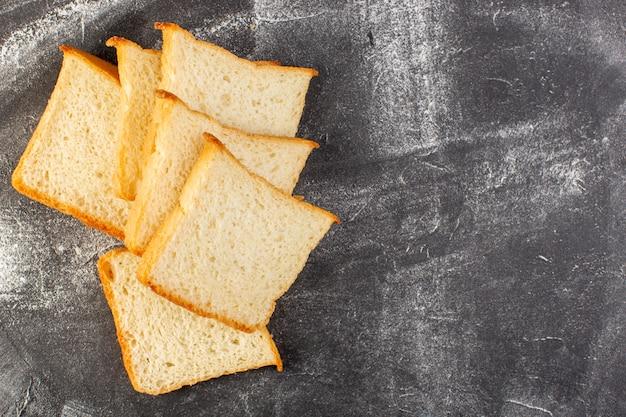 Vista superior de perto pães de pão branco fatiados e saborosos isolados no fundo cinza.