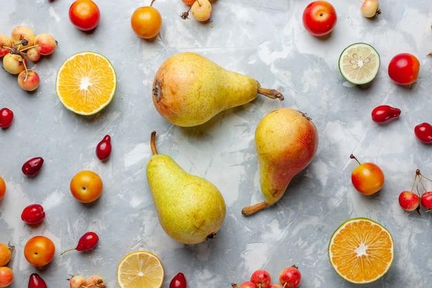 Vista superior de perto peras doces com limão e cerejas na mesa branca frutas vitamina de baga verão suave