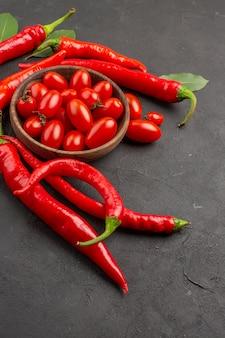 Vista superior de perto pimentas vermelhas quentes e folhas de louro e uma tigela de tomate cereja na mesa preta