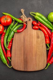 Vista superior de perto pimentões vermelhos e verdes quentes tomates uma tábua de cortar no chão preto