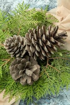 Vista superior de perto ramos de pinheiro de pinhas em xale bege em superfície escura