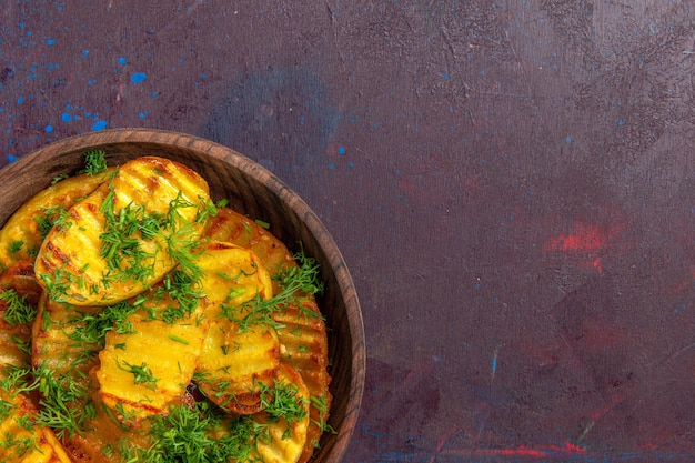Vista superior de perto saborosas batatas cozidas com verduras dentro do prato na superfície escura cozinhando batata cips jantar