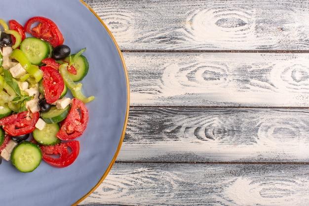 Vista superior de perto salada de legumes frescos com pepinos fatiados, tomates e azeitona dentro do prato sobre fundo cinza cor de refeição de salada de vegetais