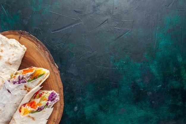Vista superior de perto sanduíche de carne um sanduíche feito de carne grelhada em um espeto cortado em uma mesa azul escura
