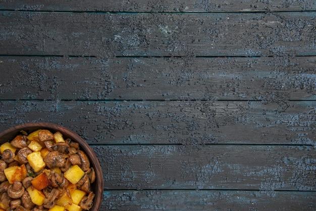 Vista superior de perto tigela de batatas e cogumelos com batatas e cogumelos na parte inferior esquerda da mesa