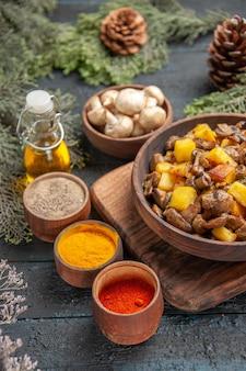 Vista superior de perto tigela de comida batatas e cogumelos em uma tigela marrom na tábua de madeira ao lado de diferentes especiarias coloridas sob óleo em galhos de árvores de garrafa e tigela de cogumelos