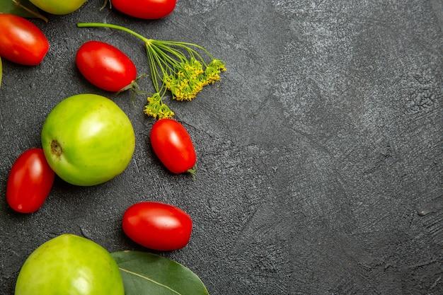Vista superior de perto tomates verdes e tomates cereja, flores de endro e folhas de louro à esquerda de um solo escuro com espaço de cópia