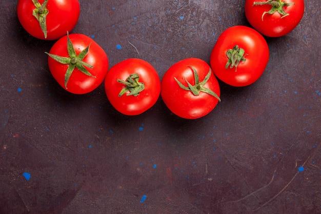 Vista superior de perto tomates vermelhos frescos circulando no espaço escuro