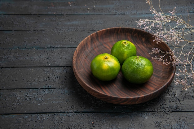 Vista superior de perto três limas em uma tigela três limas verdes em uma tigela marrom ao lado dos galhos na mesa escura Foto gratuita