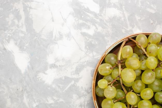Vista superior de perto uvas verdes frescas suculentas frutas suaves doces na mesa branca frutas frescas suco maduro vinho