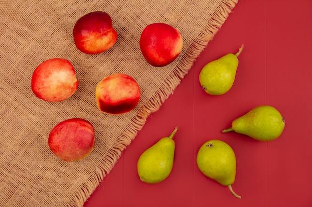 Vista superior de pêssego isolado em um pano de saco e peras em um fundo vermelho