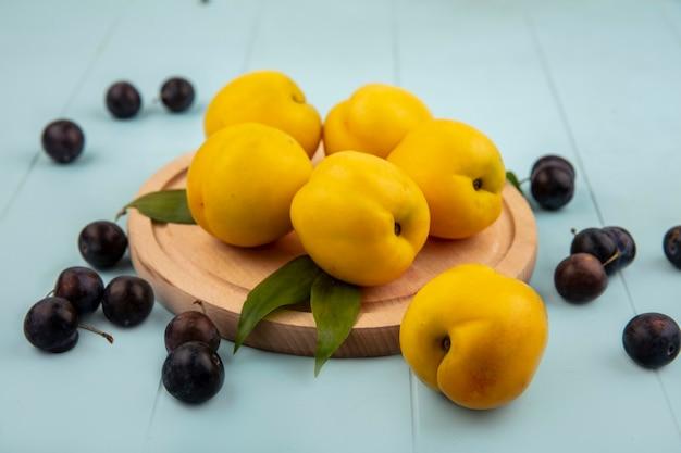 Vista superior de pêssegos amarelos em uma placa de cozinha de madeira com abrunhas azedas isoladas em um fundo azul