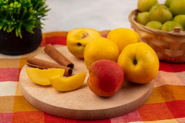 Vista superior de pêssegos amarelos em uma placa de cozinha de madeira com paus de canela e ameixas de cereja verdes em um balde em um fundo de toalha de mesa xadrez