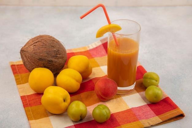 Vista superior de pêssegos amarelos frescos com ameixas verdes cereja com coco e suco de pêssego fresco em uma toalha de mesa quadriculada em um fundo branco