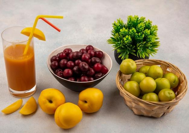 Vista superior de pêssegos amarelos frescos com suco de pêssego fresco com cerejas vermelhas em uma tigela com ameixas de cereja verdes em um balde em um fundo branco
