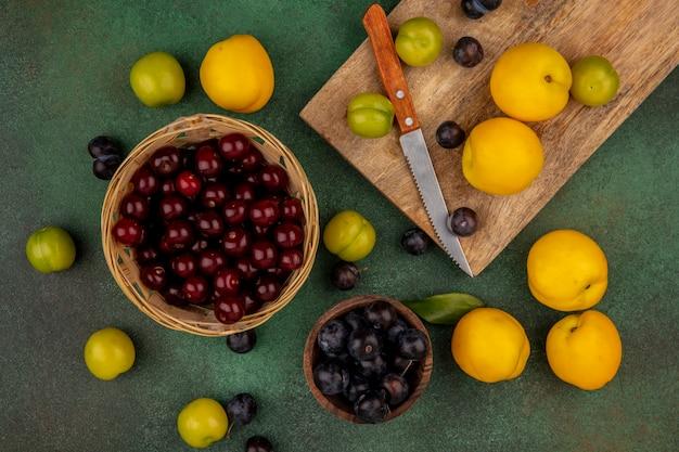 Vista superior de pêssegos amarelos frescos em uma placa de cozinha de madeira com ameixas verdes cereja com cerejas vermelhas em um balde sobre um fundo verde