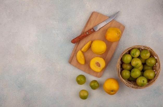 Vista superior de pêssegos amarelos frescos em uma placa de cozinha de madeira com uma faca com ameixas de cereja verdes em um balde em um fundo branco com espaço de cópia