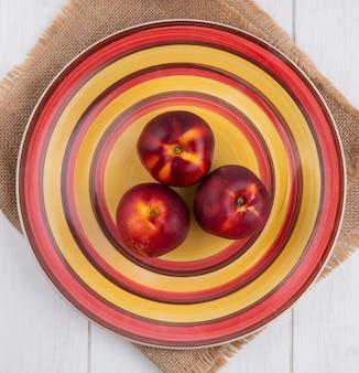 Vista superior de pêssegos em um prato amarelo-vermelho em um guardanapo bege em uma superfície branca