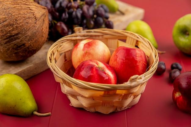 Vista superior de pêssegos frescos e suculentos em um balde com coco em uma placa de cozinha de madeira sobre um fundo vermelho