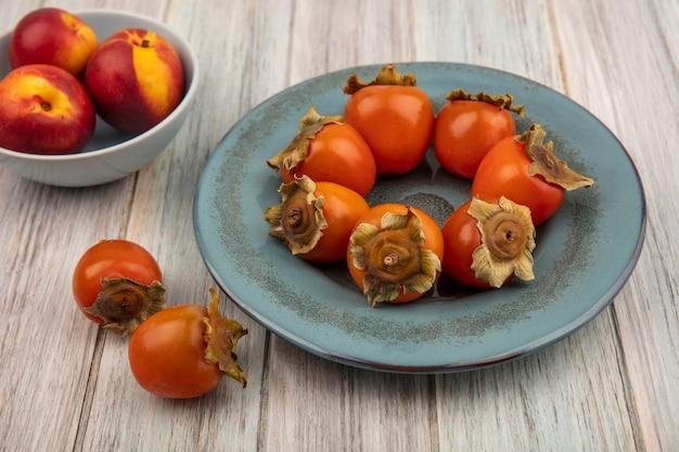 Vista superior de pêssegos orgânicos em uma tigela com caquis frescos e macios em um prato sobre um fundo cinza de madeira