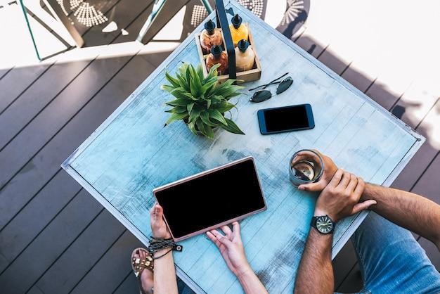 Vista superior de pessoas com gadgets em uma mesa do lado de fora