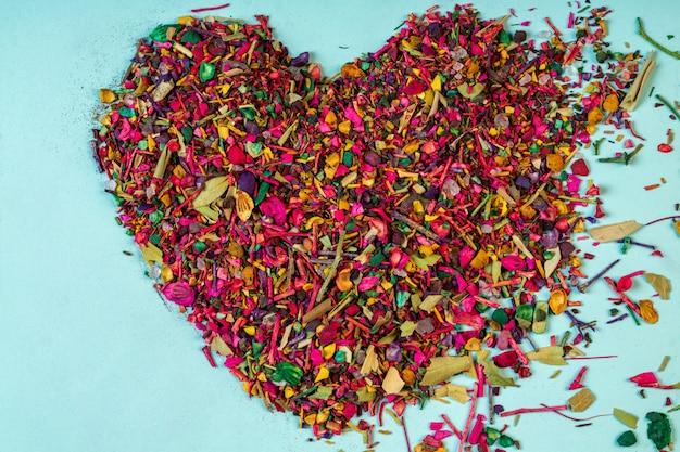 Vista superior de pétalas de flores secas multicoloridas e ervas dispostas em forma de coração em azul