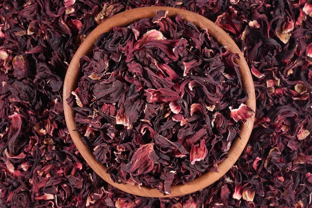 Vista superior de pétalas secas de hibisco em uma tigela de madeira