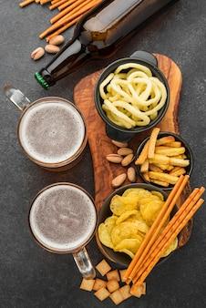 Vista superior de petiscos saborosos e canecas de cerveja