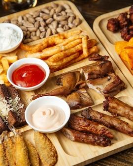 Vista superior de petiscos variados de cerveja como codornas assadas, batatas fritas, pistache e batatas fritas com molhos em uma placa de madeira
