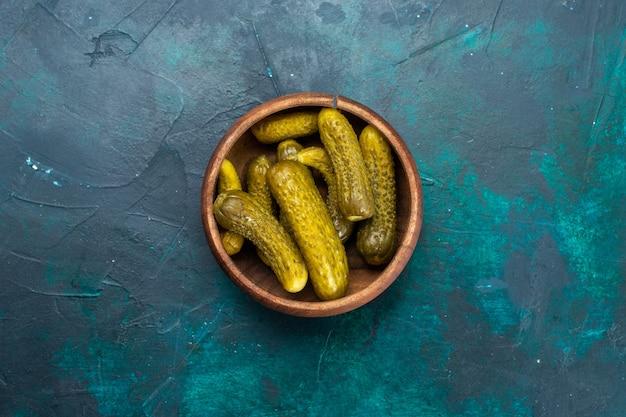 Vista superior de pickles salgados dentro de uma panela marrom redonda em uma superfície azul escura
