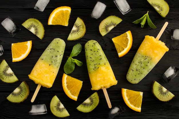 Vista superior de picolés com kiwi e frutas laranja na mesa de madeira preta. fechar-se.