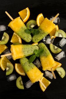 Vista superior de picolés com kiwi e frutas laranja na mesa de madeira preta.